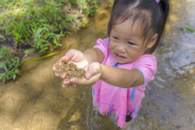 Asian Children playing  barefoot in stream water, play mud and sand. High resolution image gallery stock photos