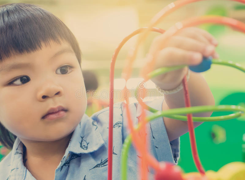 Asian children playing on educational toy stock photo