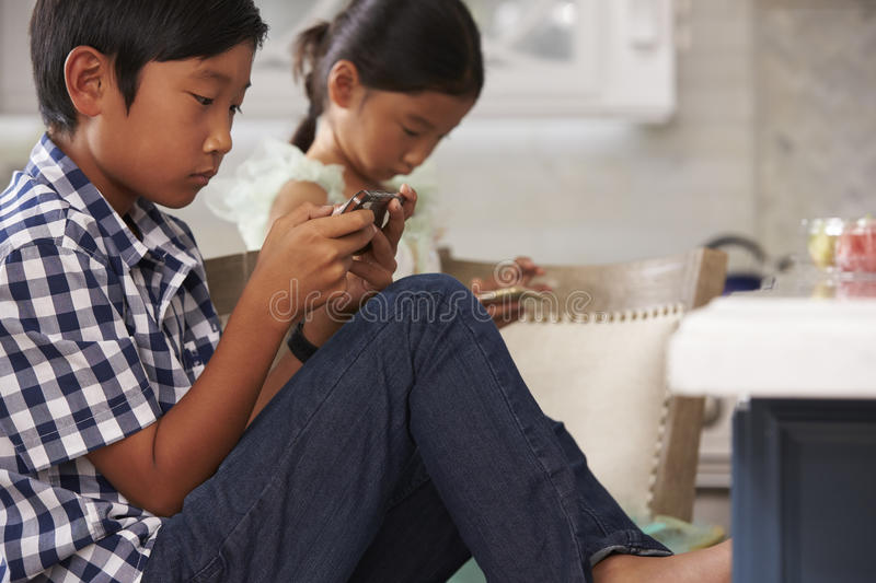 Asian Children Playing Games On Mobile Devices In Kitchen royalty free stock images