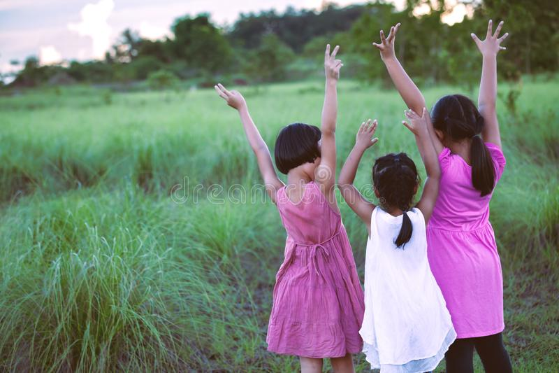 Asian children raise hands and playing together. With fun in the meadow stock photography