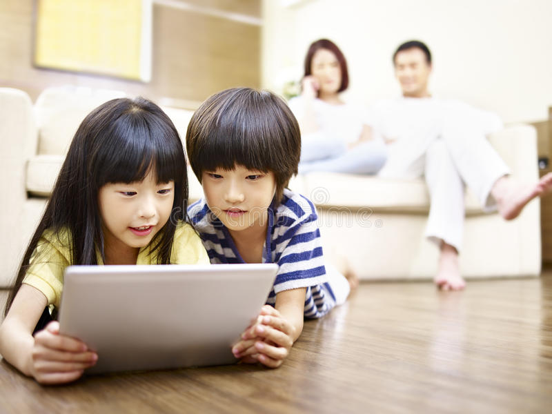Asian children using digital tablet. Two asian children lying on floor playing video game using digital tablet while parents watching in the background royalty free stock photography