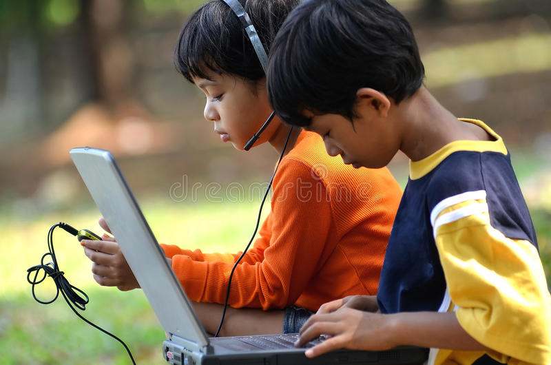 Asian Children using Gadget. Young children, boy and girl using laptop and listening to digital music in outdoor scene royalty free stock images