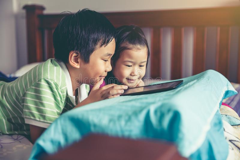 Asian children watching video and playing game on digital tablet stock image
