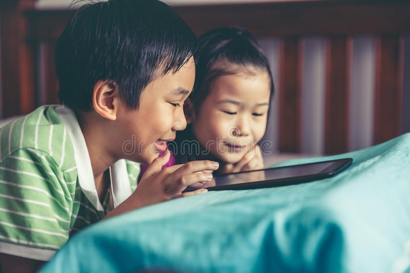 Asian children watching video and playing game on digital tablet stock photography
