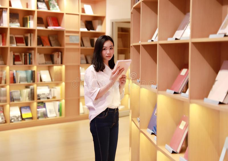 Asian Chinese beautiful pretty cute woman girl student Teenager read book in bookstore library model look at camera. Asian Chinese beautiful pretty cute woman royalty free stock images