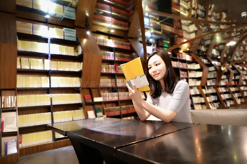 Asian Chinese beautiful pretty young cute woman girl student Teenager read book in bookstore library smile sit by a table. Asian Chinese beautiful pretty cute royalty free stock photo