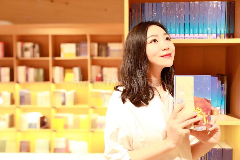 Asian Chinese beautiful pretty young cute woman girl student Teenager read book in bookstore library smile spend her pastime. Asian Chinese beautiful pretty cute royalty free stock image