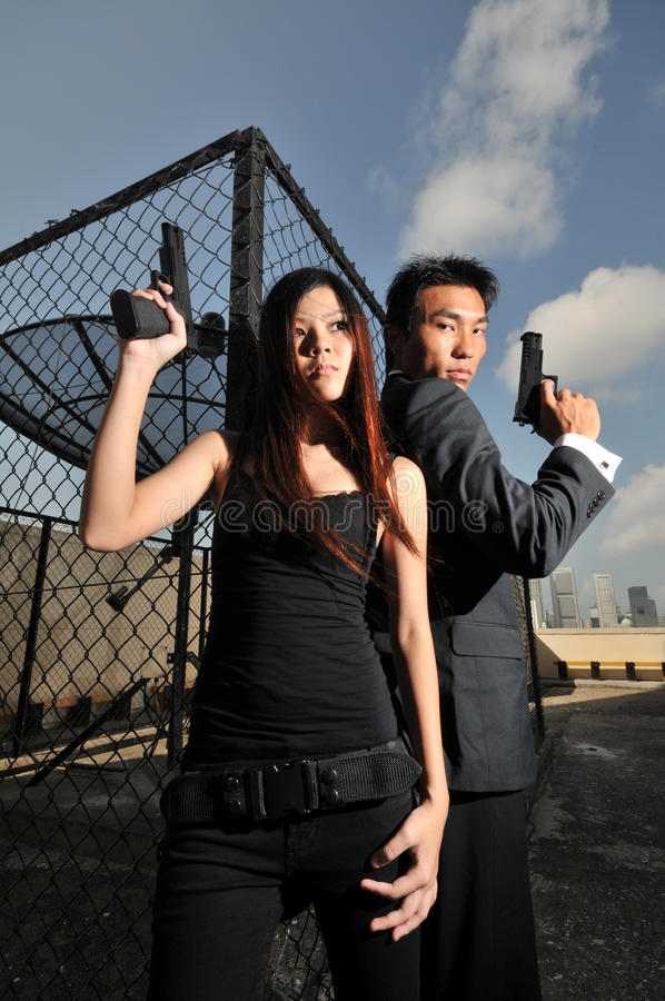 Free Asian Chinese Couple Carrying Guns On Rooftop 2 Royalty Free Stock Image - 16886706