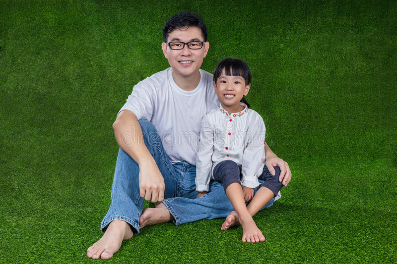 Asian Chinese father and daughter sitting on the grass stock photography