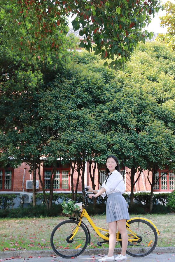 Happy Asian Chinese pretty girl riding a bike wear student suit in school. Asian Chinese freedom woman with flowers on hand in nature in spring outdoor enjoy royalty free stock photos