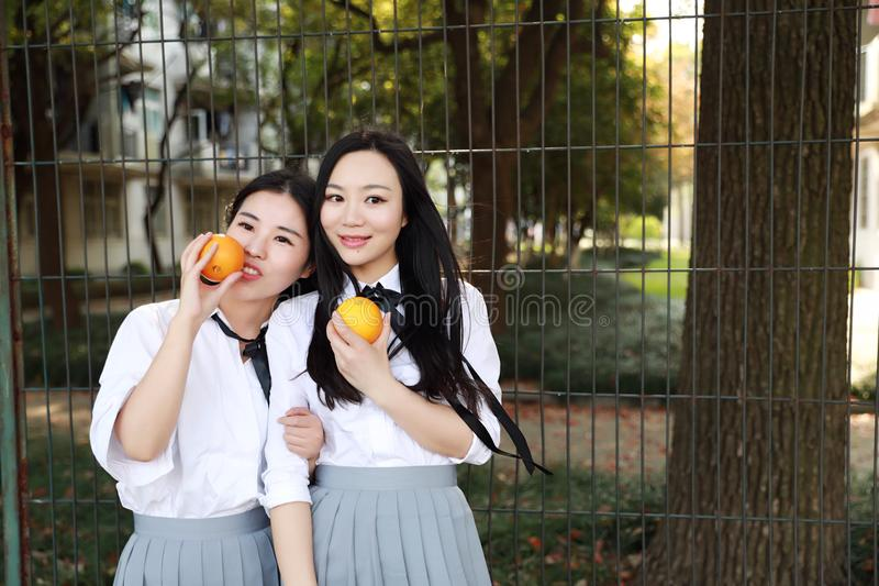 Two young Asian Chinese pretty girls wear student suit in school best friends smile laugh smell orange fruit in nature royalty free stock photo