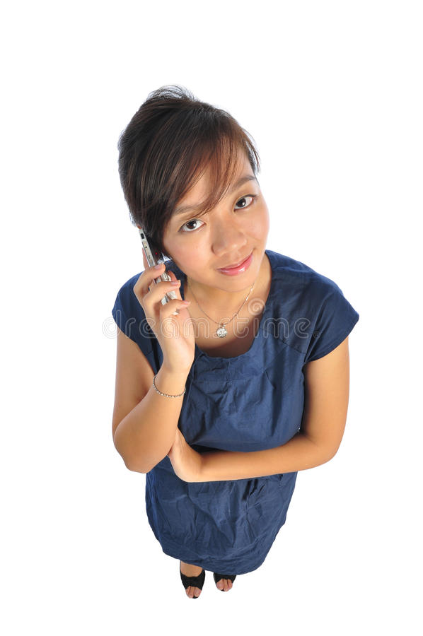 Asian chinese girl answering phonecall. Beautiful young Asian Woman picture taken from the top to give a big doll head effect stock photo