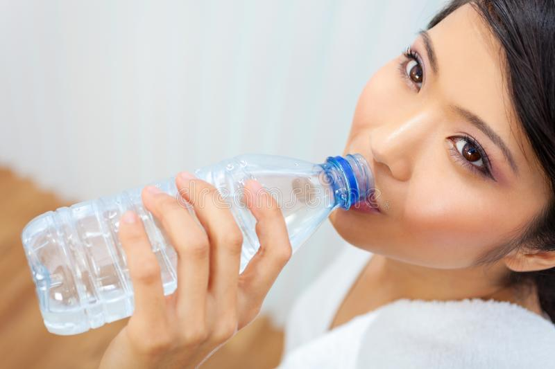 Asian Chinese Girl Drinking Bottle of Water at Gym royalty free stock photography