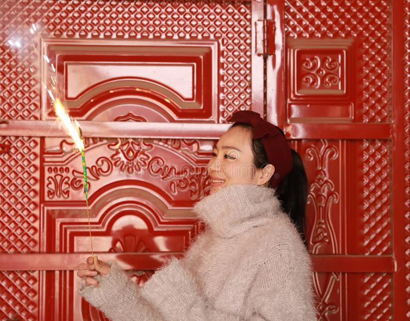 Asian chinese Girl holding sparkler firework with hand at front of red door . Brunette, looking. A pretty young girl wearing beautiful dress holding a sparkler royalty free stock image