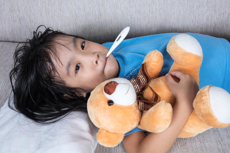Asian Chinese girl holding teddy bear for fever temperature meas. Asian Chinese little girl holding teddy bear for fever temperature measurement royalty free stock photography