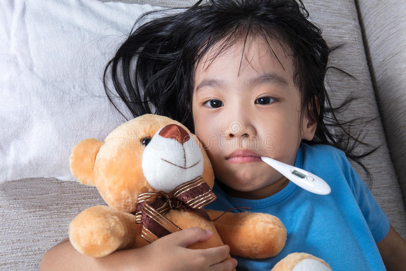 Asian Chinese girl holding teddy bear for fever temperature meas. Asian Chinese little girl holding teddy bear for fever temperature measurement royalty free stock image