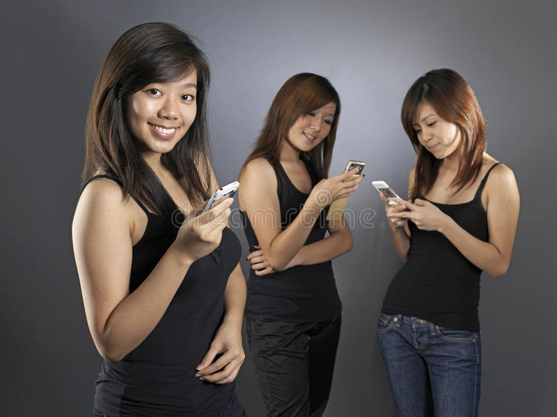 Asian chinese girls using their mobile phones stock images