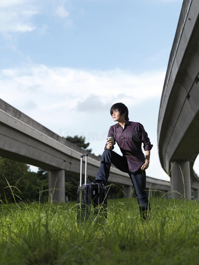 Asian Chinese guy with his luggage deciding stock photography