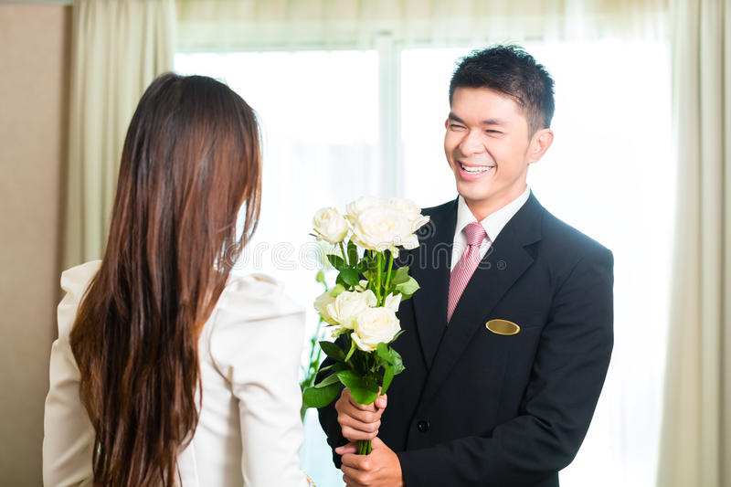 Asian Chinese hotel manager welcoming VIP guest. Asian Chinese Hotel Manager or director or supervisor welcome arriving VIP guest with roses on arrival in luxury royalty free stock images
