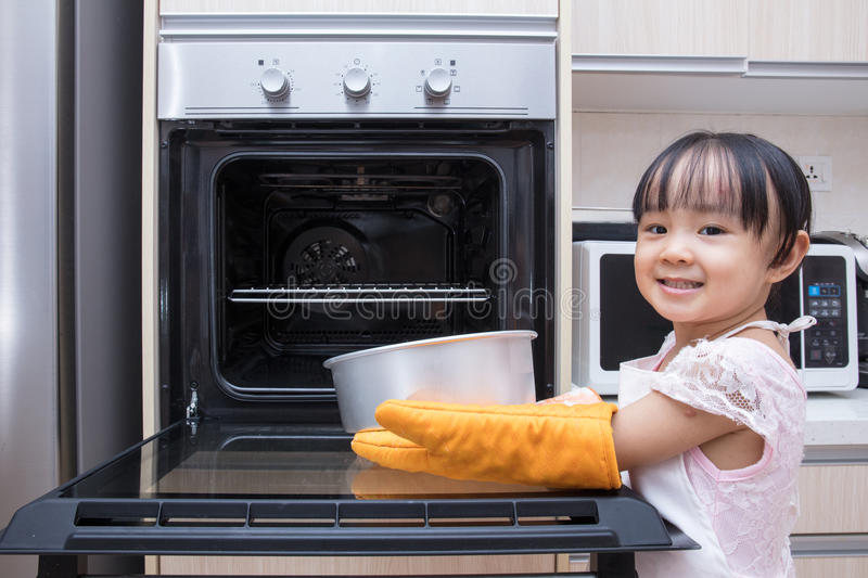 Asian Chinese little girl baking cake. At home in the kitchen stock photography