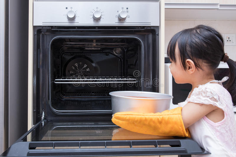 Asian Chinese little girl baking cake. At home in the kitchen stock image