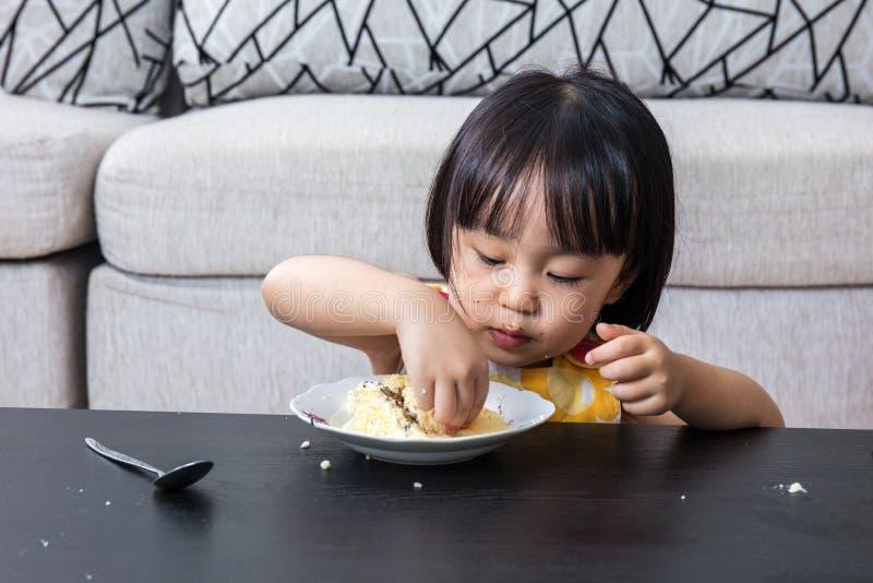 Asian Chinese little girl eating birthday cheese cake stock photo