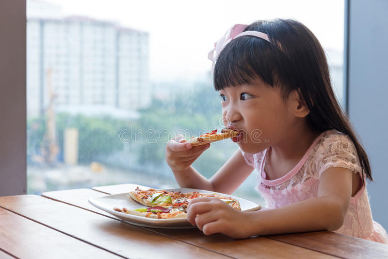Asian Chinese little girl eating pizza pepperoni stock photography