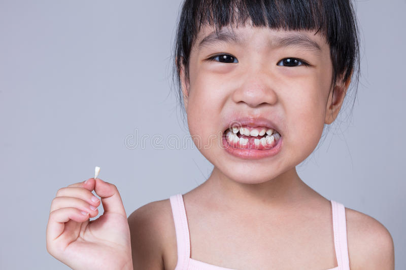 Asian Chinese little girl holding her missing tooth. In isolated white background stock images