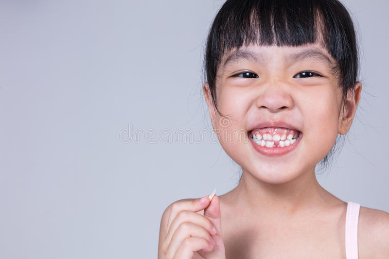 Asian Chinese little girl holding her missing tooth. In isolated white background royalty free stock photography