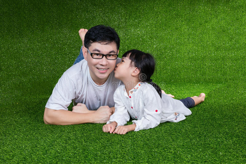 Asian Chinese little girl kissing her father stock photo
