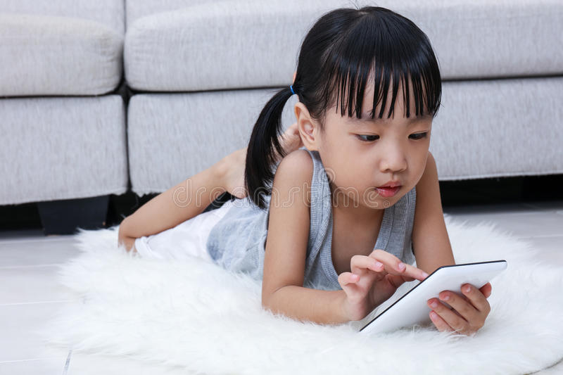 Asian Chinese little girl playing phone on the floor royalty free stock image