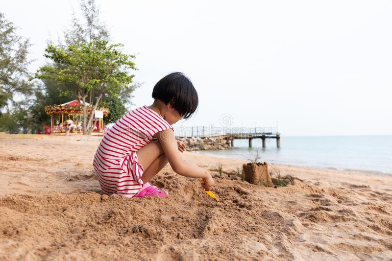 Asian Chinese little girl playing sand at beach royalty free stock photo