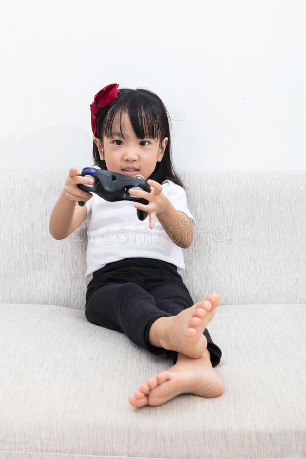 Download Asian Chinese Little Girl Playing TV Games On The Sofa Stock Photo - Image: 83702582