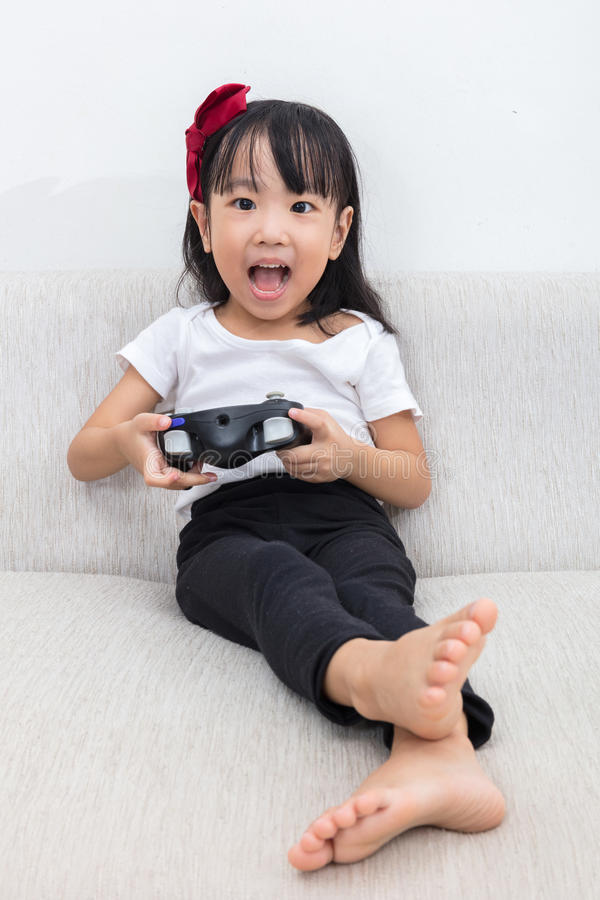 Download Asian Chinese Little Girl Playing TV Games On The Sofa Stock Photo - Image: 83703138