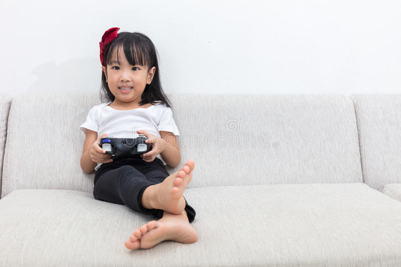 Download Asian Chinese Little Girl Playing TV Games On The Sofa Stock Image - Image: 83703695