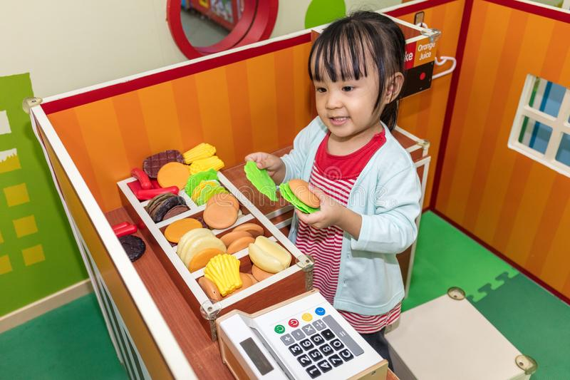 Asian Chinese little girl role-playing at burger store. At indoor playground stock photography