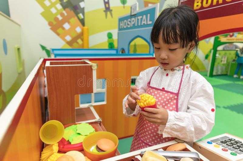 Asian Chinese little girl role-playing at burger store royalty free stock photos