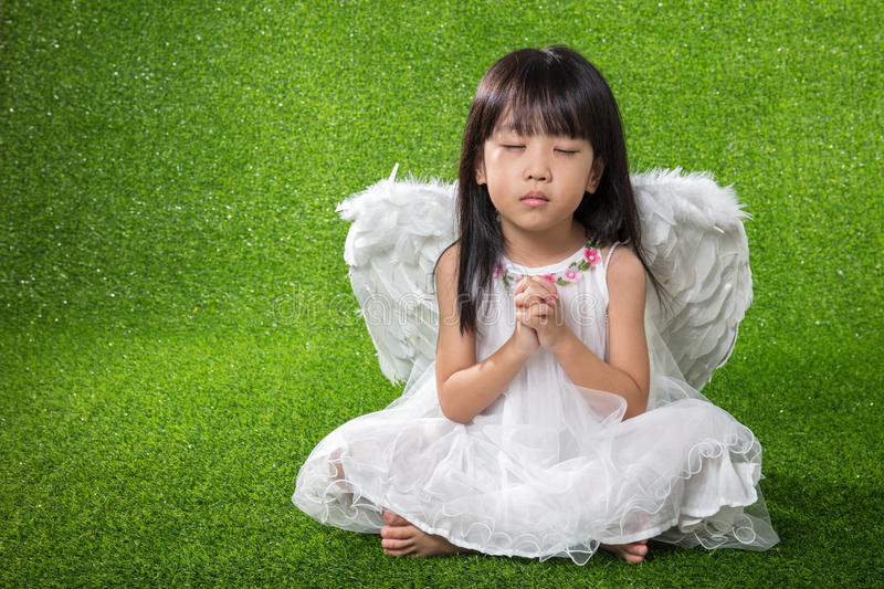 Asian Chinese little girl wearing angel wings and praying stock photo