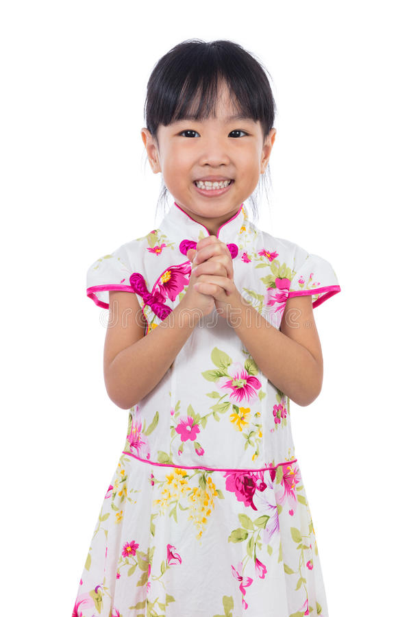 Asian Chinese little girl wearing cheongsam with greeting gesture royalty free stock photo