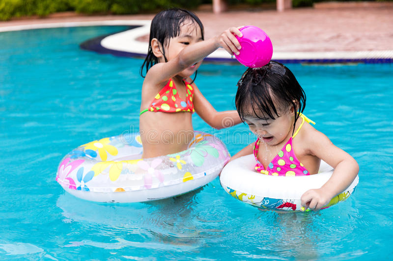 Asian Chinese Little Girls Playing in the Swimming Pool royalty free stock image