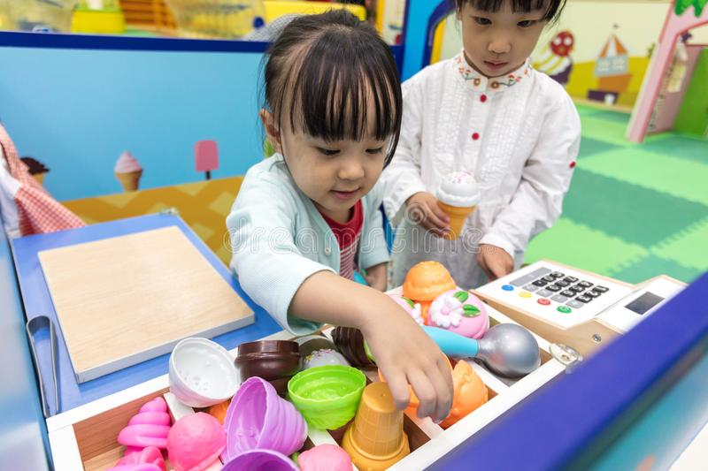 Asian Chinese little girls role-playing at ice cream store. At indoor playground stock image