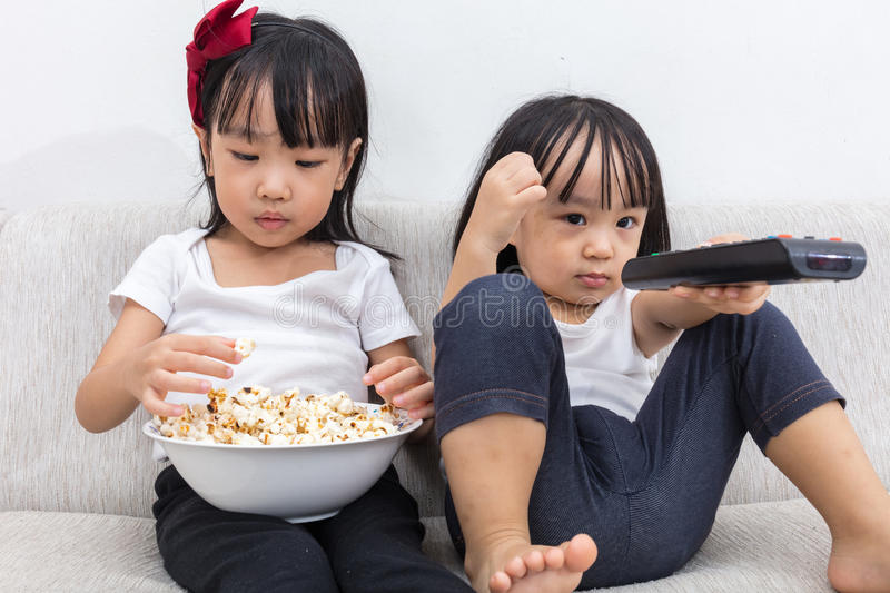 Download Asian Chinese Little Sisters Eating Popcorn On The Sofa Stock Image - Image: 83709167