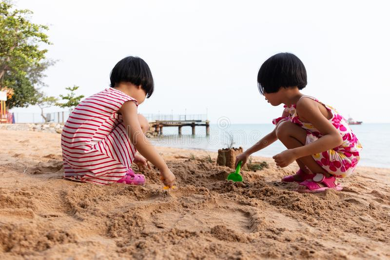 Asian Chinese little sisters playing sand at beach royalty free stock images