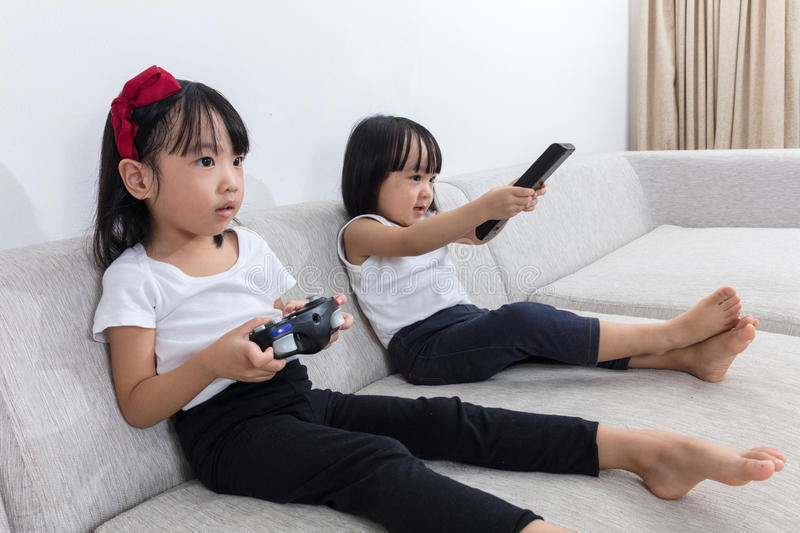 Download Asian Chinese Little Sisters Playing TV Games On The Sofa Stock Photo - Image: 83708438
