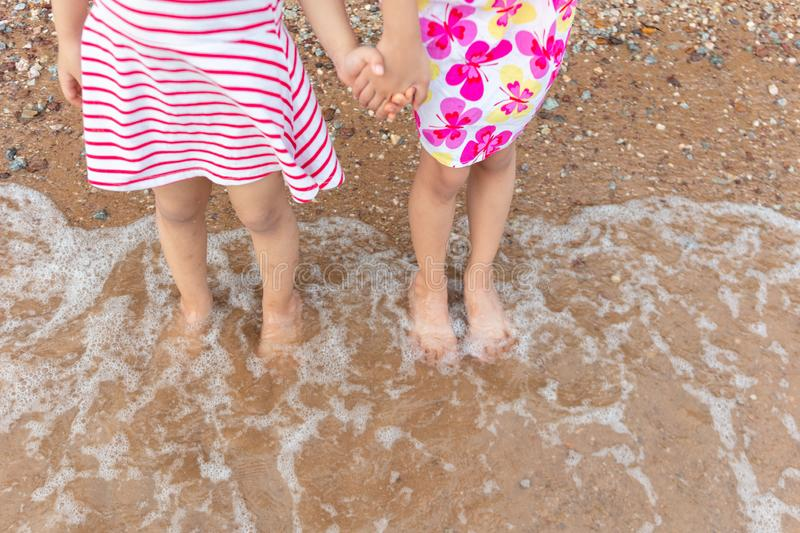 Asian Chinese little sisters playing water at beach royalty free stock photography