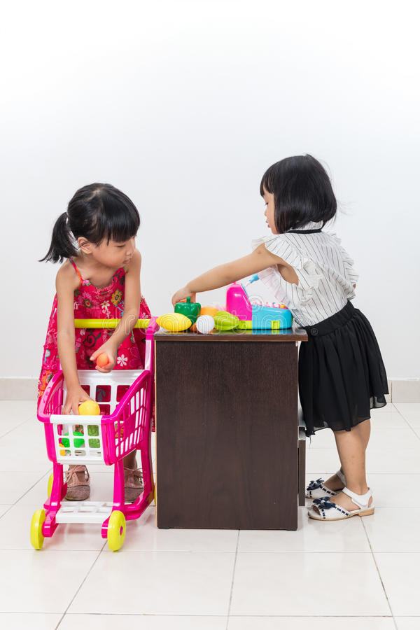 Asian Chinese little sisters pretending customer and cashier wit. Asian Chinese little sisters pretending as customer and cashier with trolley toys in isolated royalty free stock photos