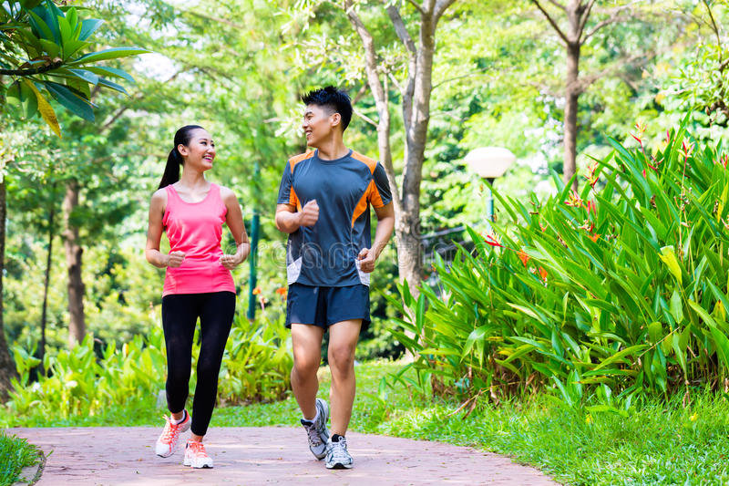 Asian Chinese man and woman jogging in city park stock images