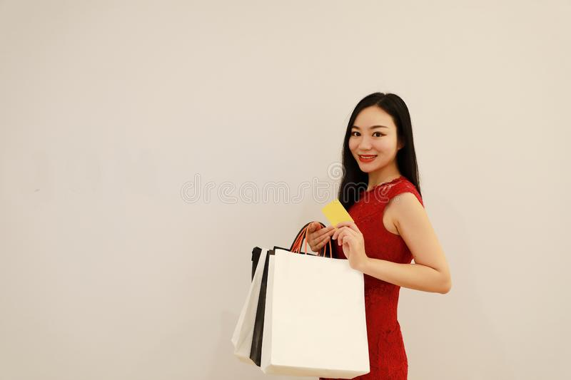 Asian Chinese modern fashionable woman girl shopping card and bag on hand in a mall white isolated background royalty free stock photos