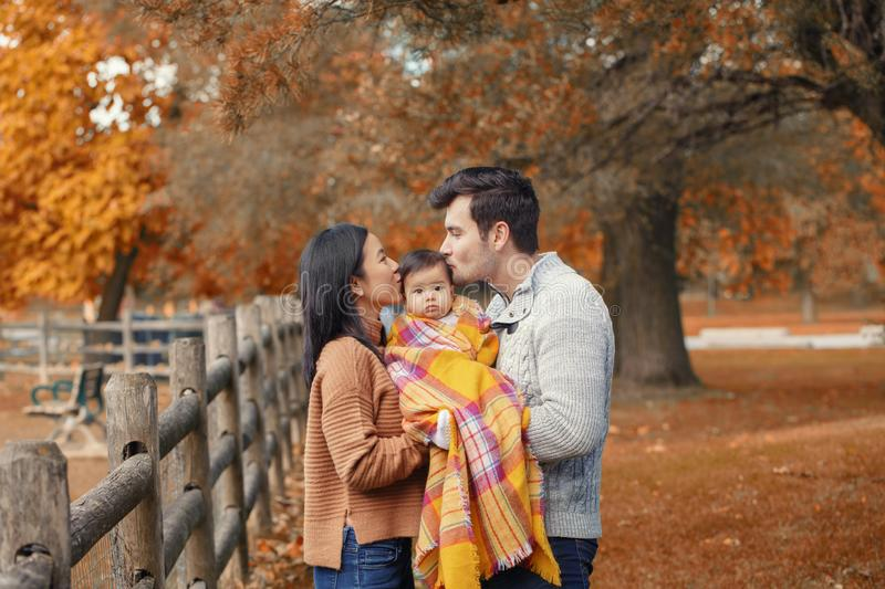 Asian Chinese mother and Caucasian father dad holding kissing baby girl wrapped in blanket royalty free stock images