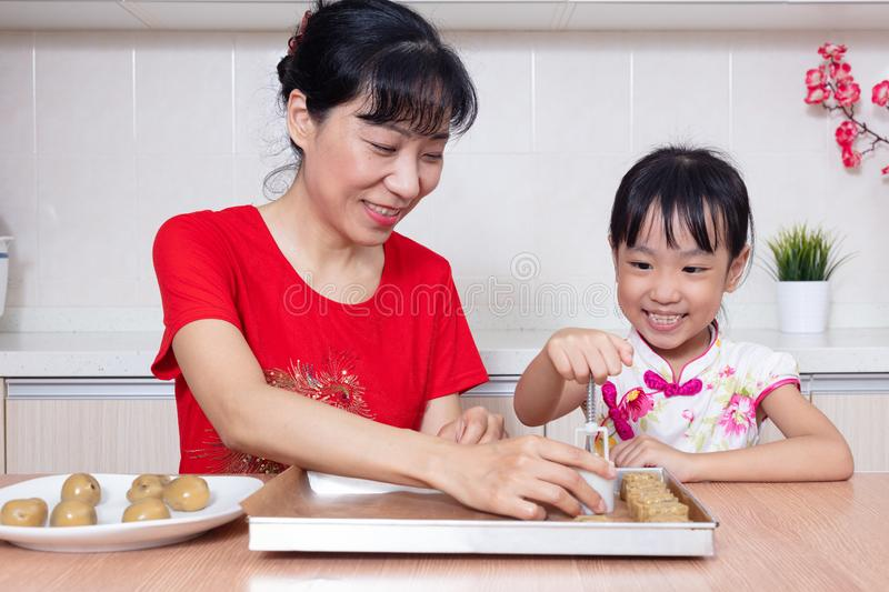 Asian Chinese mother and daughter making moon cake in the kitchen royalty free stock image